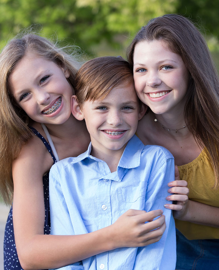 three young kids smiling while wearing braces